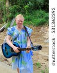Small photo of Epi island, Vanuatu-October 5, 2014: Albino girl with blue guitar makes the pedestrian route between Lamen Bay and Nikaura villages from the E.shore to the W.across the island. Shefa province-Vanuatu.