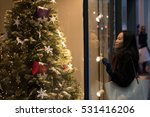 Small photo of An Asian girl stops in front of a window shop to admire a beautiful Christmas tree displayed under the warm lights in Edinburgh City center, Scotland, United Kingdom, as her hair is blown by the wind.