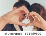 Small photo of Romantic couple in love gesturing a heart with fingers