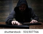 Small photo of hacker in the black hood in a room with wooden walls