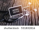 Small photo of Stethoscope on wood with immune system word as medical concept.