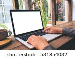 Stock photo mockup image of hands using laptop with blank white screen on vintage wooden table in cafe 531854032