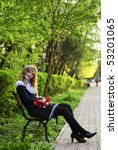 blonde girl in garland from daisies sit on behcn in park, outdoor portrait - stock photo