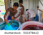 Small photo of DHAKA, BANGLADESH - MAY 23, 2016: Textile factory dyehouse where three underaged children are mixing the local garments with dyestuff to color the garments