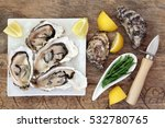 Small photo of Oysters on crushed ice on a square china plate with oyster knife, samphire and lemon fruit on old wooden background.