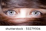 Small photo of estrange look of a young woman with blue eyes with her hair around the eyes