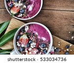Small photo of acai pink smoothie bowls on cutting board.