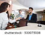 Stock photo two business man arriving to hotel give meeting woman receptionist credit card pay room 533075038