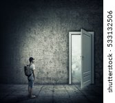 Small photo of Abstract idea with a person standing in a dark room, in front of a opened door. Escape opportunity, entrance to another world.