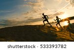 Stock photo group of athletes two girls and a guy are fleeing the mountain near river at dusk 533393782