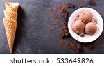 Stock photo plate of chocolate ice cream scoops with pieces of chocolate bar and waffle cones on dark 533649826