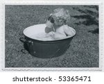 Vintage photo (1955) of baby taking a bath in a washtub - stock photo