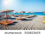 Small photo of Sea panorama, overlooking the blue sea and beach with a yellow sun beds and umbrellas, Rhodes, Greece