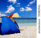 Tent and umbrella as a sun protectionatn an ocean beach - stock photo