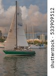 Small photo of Honolulu, Hawaii, USA, Dec. 11, 2016: Green sailboat with gold and white sails in the Ala Wai Harbor.