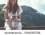 Small photo of Cheerful woman sitting on the fence with mobile phone. High mountains touristic path. Digital communication. Texting with friends in social network