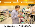 Stock photo  man shopping in supermarket reading product information using smarthone 534141856