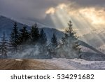 stormy winter sky over spruce forest in fog by the road at the mountain hill - stock photo