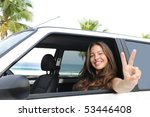 car rental: happy woman in her car near the beach showing victory sign - stock photo