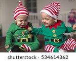 Small photo of Happy twin babies elf helper of Santa in costume at home in living room