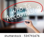 Small photo of Woman Hand Writing Who Is Accountable? with a marker over transparent board. Isolated on Office. Business concept. Stock Image