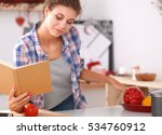 Young Woman Reading Cookbook I...