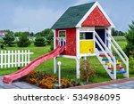 wooden children playhouse with slides in backyard spring garden