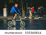 BARCELONA, SPAIN - DECEMBER 25, 2015: Christmas morning, person riding a bike with Santa Claus cap - stock photo