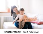 mother dressing her daughter in ... | Shutterstock . vector #535739362