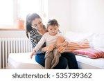 mother dressing her daughter in ... | Shutterstock . vector #535739362