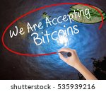 Small photo of Woman Hand Writing We Are Accepting Bitcoins with marker over transparent board. Isolated on nature. Business concept. Stock Photo