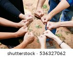Small photo of Posting stranglehold or wisp hand to the center of group of people in circle to represent victory, fight, unity, collaborative, teamwork.