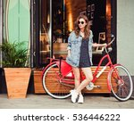 Small photo of Cute girl in a summer dress, denim jacket, sunglasses stands with red vintage bicycle in a European city. Sunny summer. On background surf cafe.