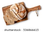 freshly baked bread on wooden cutting board isolated on white background, top view
