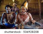 Small photo of YOUW VILLAGE, ATSY DISTRICT, ASMAT REGION, IRIAN JAYA, NEW GUINEA, INDONESIA - MAY 23, 2016: Man with a drum in the house. Man from the tribe of Asmat with traditional face painting beats the drum
