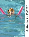 Young girl in swimming pool swimming with floating device - stock photo