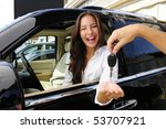 businesswoman receiving keys of her new status car from dealer - stock photo