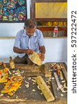 Small photo of AMBALANGODA, SRI LANKA - DECEMBER 5, 2016: The artisan in process of mask making in the workshop of the Mask Museum, on December 5 in Ambalangoda.