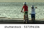 Two Children On Bike By The Sea
