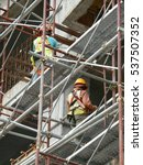 Small photo of SEREMBAN, MALAYSIA -SEPTEMBER 05, 2016: Construction workers wearing safety harness and adequate safety gear while working at high level at the construction site in Seremban, Malaysia.