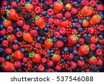 Berries overhead closeup colorful assorted mix of strawberry, blueberry, raspberry, blackberry, red currant in studio on dark background