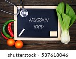 Small photo of Top or flat lay view of mustard, tomatoes, chili, stethoscope and black chalkboard written with AFLATOXIN FOOD on wooden background. Healthcare concept.