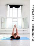 Small photo of Sporty man practicing yoga in white room with big window. Agni stambhasana. Firelog pose