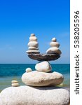 Small photo of Concept of harmony and balance. Balance stones against the sea. Rock zen in the form of scales