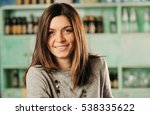 young woman smiling in a pub | Shutterstock . vector #538335622