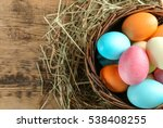 Wicker basket with colorful Easter eggs on wooden table, closeup
