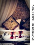 Small photo of Two turkish tea cups and turkish delight with oriental canopy bed at the background. Silver tray. Romantic concept. Valentines background. Arabian nights ambiance. Vertical, toned