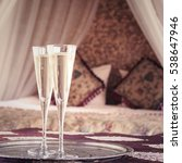 Small photo of Two champagne glasses with oriental canopy bed at the background. Romantic concept. Valentines background. Arabian nights ambiance. Square, glasses on left side, more defined background, toned