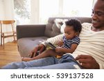 father and son sitting on sofa... | Shutterstock . vector #539137528