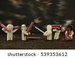Small wooden males are playing with bangers - stock photo